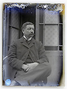 deteriorating glass plate with man sitting outside in front of door Paris 1900s