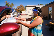 "02 SEPTEMBER 2020 - MITCHELLVILLE, IOWA: FILIPINA SILVER, who works at the library in Mitchellville, delivers a hot meal to person in a car at the library. There is no grocery store in Mitchellville, a small community in eastern Polk County. It doesn't qualify as a ""food desert"" under USDA guidelines because there are grocery stores within 10 miles in neighboring communities, but based on state data, Mitchellville is the poorest community in Polk County (which includes the Des Moines metropolitan area). The Mitchellville zip code has the lowest per capita income in Polk County. Many people don't own cars and can't get to neighboring communities to buy groceries. The library in Mitchellville has made arrangements with a neighboring community. Every day someone from the Mitchellville library picks up hot meals from a nearby town and distributes them in the library parking lot.      PHOTO BY JACK KURTZ"