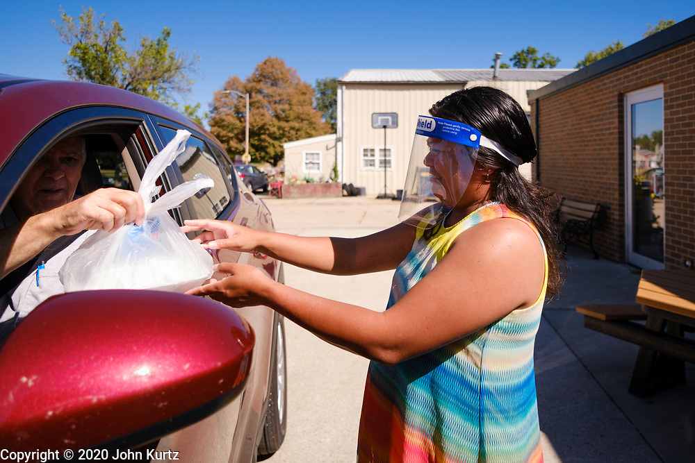 """02 SEPTEMBER 2020 - MITCHELLVILLE, IOWA: FILIPINA SILVER, who works at the library in Mitchellville, delivers a hot meal to person in a car at the library. There is no grocery store in Mitchellville, a small community in eastern Polk County. It doesn't qualify as a """"food desert"""" under USDA guidelines because there are grocery stores within 10 miles in neighboring communities, but based on state data, Mitchellville is the poorest community in Polk County (which includes the Des Moines metropolitan area). The Mitchellville zip code has the lowest per capita income in Polk County. Many people don't own cars and can't get to neighboring communities to buy groceries. The library in Mitchellville has made arrangements with a neighboring community. Every day someone from the Mitchellville library picks up hot meals from a nearby town and distributes them in the library parking lot.      PHOTO BY JACK KURTZ"""