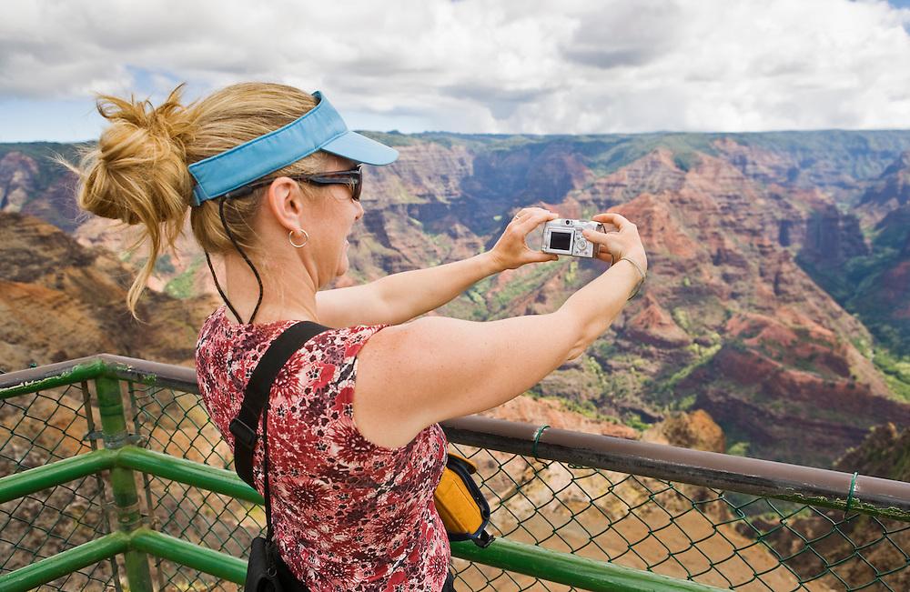 Middle aged woman taking a digital picture from a viewpoint overlooking Waimea Canyon, Waimea Canyon State Park, Kauai, Hawaii, USA.