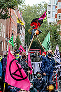XR activist stands in a wooden tripod as hundreds of fellow Extinction Rebellion climate protestors blocked Tufton Street, outside Tufton Court in central London on Wednesday, Sept 2, 2020. Over 90 people have been arrested so far as Extinction Rebellion protesters swarm central London. (VXP Photo/ Vudi Xhymshiti)