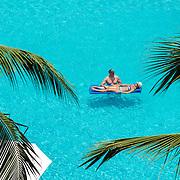 Couple with floatie on the pool. Marriott CasaMagna Puerto Vallarta. Jalisco, Mexico.