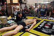 Japanese tattoo artist at work on a stage at the 2nd International Tattoo Convention in London on Saturday, Oct. 7, 2006, in London, UK. With over 15.000 visitors in three days during the 2005 edition, the event placed London in a central position in the tattoo world.  This year about 150 artists ,representing all the tattoo styles, are ticking away with their machines in a very exciting atmosphere. **ITALY OUT**....