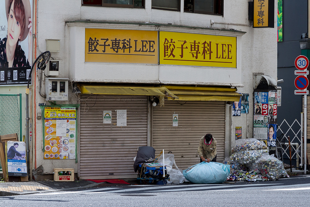 A homeless person sorts their collection of recycled material, that they collect for money, outside a shuttered shop in the back streets of Shinjuku, Tokyo, Japan. Saturday June 12th 2021