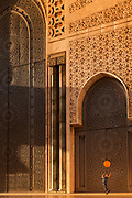 Boy playing with balloon by Hassan II Mosque in Casablanca, Morocco