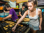 "06 FEBRUARY 2015 - BANGKOK, THAILAND: Workers at Thanusingha Bakery pull traditional Thai Catholic desert cakes out of the baking pans. The cakes are called ""Kanom Farang Kudeejeen"" or ""Chinese Monk Candy."" The tradition of baking the cakes, about the size of a cupcake or muffin, started in Siam (now Thailand) in the 17th century AD when Portuguese Catholic priests accompanied Portuguese soldiers who assisted the Siamese in their wars with Burma. Several hundred Siamese (Thai) Buddhists converted to Catholicism and started baking the cakes. When the Siamese Empire in Ayutthaya was sacked by the Burmese the Portuguese and Thai Catholics fled to Thonburi, in what is now Bangkok. The Portuguese established a Catholic church near the new Siamese capital. Now just three families bake the cakes, using a recipe that is 400 years old and contains eggs, wheat flour, sugar, water and raisins. The same family has been baking the cakes at the Thanusingha Bakery, near Santa Cruz Church, for more than five generations. There are still a large number of Thai Catholics living in the neighborhood around the church.        PHOTO BY JACK KURTZ"