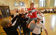 """Up2Us Coach Across America coaches Ski Bailey (R) and Dr. Ajamu Banjoko (C) carry Up2Us Center Vice President Megan Bartlett on their shoulders as Laureus USA and Mercedes-Benz USA celebrate """"Healthy Futures""""-Up2Us' National Coach Training Institute at Wells Senior High School on March 4, 2014 in Chicago, Illinois.  (Getty Images for Laureus)"""