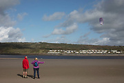 People flying a kite at Poppit Sands near St Dogmaels, Pembrokeshire, Wales, United Kingdom. St Dogmaels is a village, parish and community in Pembrokeshire, Wales, on the estuary of the River Teifi, a mile downstream from the town of Cardigan in neighbouring Ceredigion. A little to the north of the village, further along the estuary, lies Poppit Sands beach.
