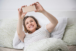 Pregnant woman lying in bed and taking selfie on mobile phone, Munich, Bavaria, Germany