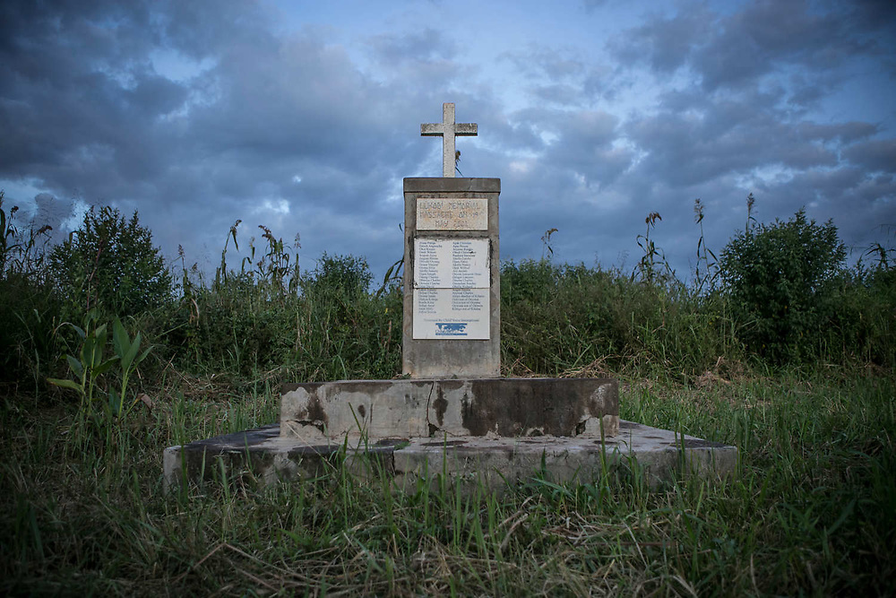 A memorial for the 2004 Lukodi massacre stands in the grass plot as about sixty villagers' dead bodies are buried underneath it in Northern Uganda. The rebel movement began by Joseph Kony's Lord's Resistance Army (LRA) that started in 1987 killed more than 100,000 civilians and abducted between 60,000 and 100,000 children until 2009, mostly Acholi people. Among the children, girls were used as soldiers and sex slaves of their commanders. Many of them escaped or were freed by LRA, but still live in poverty with children who were born in the bush and by new husbands.