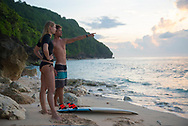 Bali, Indonesia - February 22, 2017: A couple from the Czech Republic, on holiday in Bali, surf at sunrise at Green Bowl Beach, located on Bali's Bukit Peninsula.