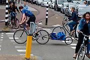 In Utrecht rijdt een fietskoerier met een aanhanger.<br /> <br /> In Utrecht a bike messenger rides with a trailer.