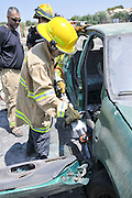 Firefighters use power tools to rescue trapped passengers from a car