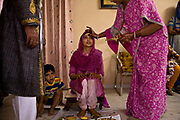 Shweta Singhal begins the preparations and rituals of her three day wedding ceremony in her home in Jaipur, here her forehead is being marked with sandlewood, after it has been smeared in saffron, dried tumeric, and vermillion, her faced is bathed in buttermilk by her family, Rajasthan, India.