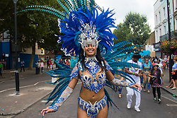 London, August 29th 2016. A woman dances her way along the procession route on Ladbroke Grove during day two of Europe's biggest street party, the Notting Hill Carnival.