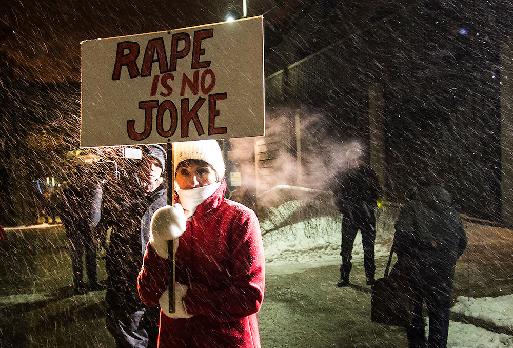 """A woman holding a sign that reads """"Rape is No Joke"""" protests as people walk in to the Centre In The Square venue where Bill Cosby is performing in Kitchener, January 7, 2015.  Bill Cosby, the subject of more than a dozen sex abuse allegations over the past three months, will go ahead with three Canadian shows this week, coming as more women levelled accusations against the comedian."""