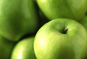 Close up selective focus photograph of a pile of Granny Smith Apples