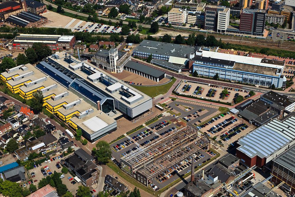 Nederland, Overijssel, Hengelo, 30-06-2011; Hart van Zuid met Lansinkveld. De fabriekshal van voormalige gieterij van Stork, nu ROC Twente (met gele zonweringen). Het voormalig Hijsch-complex, waarvan de spanten nog staan, is parkeerterrein. Rechtsonder het kerngebied met fabrieken  en kantoren van Stork en Siemens. Het gebouw met de toren is de Brandweerkazerne. .railway station and Lansinkveld, part of the 'Heart of South' development scheme. The former foundry of Stork is now ROC Twente (technical and vocational training). The former Hijsch complex, its rafter still standing, is used for parking. The building with the tower is the new fire station..luchtfoto (toeslag), aerial photo (additional fee required).copyright foto/photo Siebe Swart