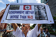 27 AUGUST 2013 - BANGKOK, THAILAND: A protester holds up a sign comparing Thai Prime Minister Yingluck Shinawatra to Hitler and the Nazi's during an anti-government protest in front of the British embassy in Bangkok. He said Yingluck has betrayed the Thai people just as the Nazis betrayed the Germans. About 25 people, including at least two British citizens, picketed the embassy Tuesday morning. They were protesting against former British Prime Minister Tony Blair, who is expected to speak to a political reform commission established by Thai Prime Minister Yingluck Shinawatra. The protest leaders were invited in to the Embassy grounds to speak to representative of the British government. The protest disbanded afterwards. No one was arrested during the protest, which lasted a little over an hour.       PHOTO BY JACK KURTZ