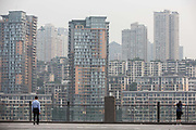 A man walks along a viewing platform in front of residential buildings in Chongqing, China, on Tuesday, May 31, 2016. The municipality of 30 million peoples state-led development approach fueled growth of 11 percent last year, the fastest pace nationwide, with President Xi Jinping praising policy innovations that have included subsidized housing and relaxed residency rules that encourage labor mobility.