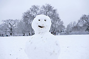 Happy snow man in Kings Heath Park on 24th January 2021 in Birmingham, United Kingdom. Deep snow arrived in the Midlands giving some light relief and fun during the current lockdown for people who simply enjoyed the weather.
