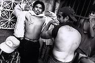 Gang members show tattoos at the La Mesa Penitentiary in Tijuana, Mexico.  1994