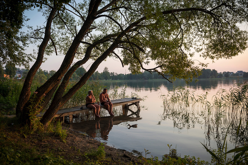 Trakai, Lithuania - August 8, 2015: At the end of a beautiful summer day, a man and woman sit and smoke cigarettes on a dock at Totoriskiu Lake in Trakai, Lithuania.