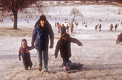 Snow scene at Wollaton Hall in Nottingham with children sledging,