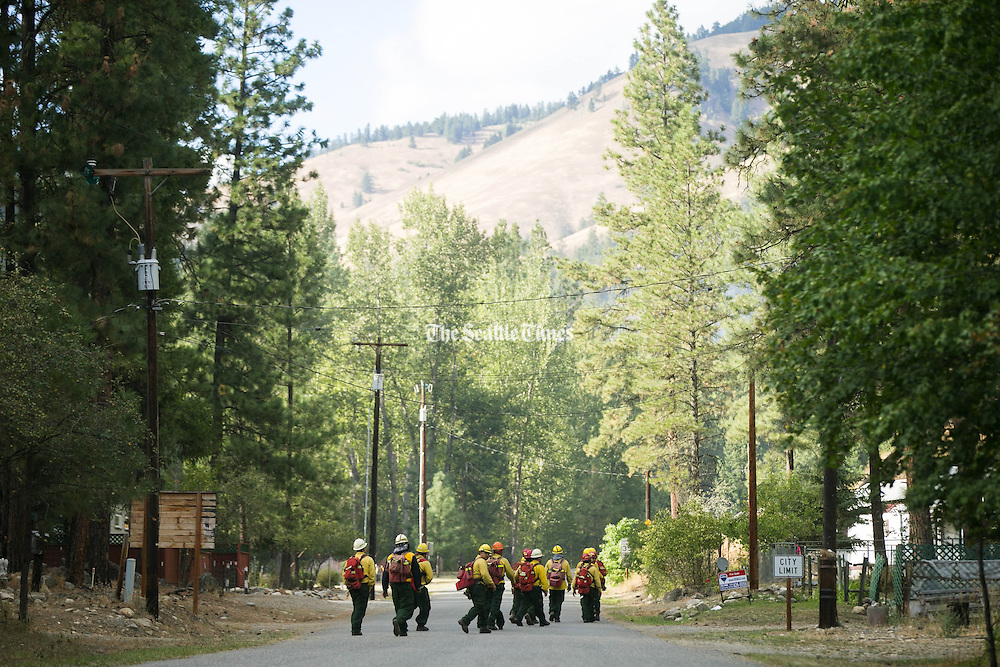 Wildland firefighters walk down North Main Street in Conconully Friday August 21, 2015 to take their positions and hold a fire line. <br /> <br /> Bettina Hansen / The Seattle Times
