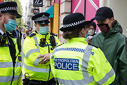 London, UK. 11th May, 2021. A Metropolitan Police officer prepares to search an activist during a protest by Palestine Action outside the UK headquarters of Elbit Systems, an Israel-based company developing technologies used for military applications including drones, precision guidance, surveillance and intruder-detection systems. The activists were protesting against the company's presence in the UK and in solidarity with the Palestinian people following attempts at forced evictions of Palestinian families in the Sheikh Jarrah neighbourhood of East Jerusalem, the deployment of Israeli forces against worshippers at the Al-Aqsa mosque during Ramadan and air strikes on Gaza which have killed several children.