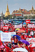 """26 MARCH 2009 -- BANGKOK, THAILAND: Anti-government protestors gather in front of the """"Grand Palace,"""" historically the seat of the Thai Monarchy. More than 30,000 members of the United Front of Democracy Against Dictatorship (UDD), also known as the """"Red Shirts""""  and their supporters gathered on Sanam Luang (the vast open field in front of the Palace) and descended on central Bangkok March 26 to start a series of protests against and demand the resignation of current Thai Prime Minister Abhisit Vejjajiva and his government. The protest is a continuation of protests the Red Shirts have been holding across Thailand. Thaksin was deposed in a coup and went into exile rather than go to prison after being convicted on corruption charges. He is still enormously popular in rural Thailand.  PHOTO BY JACK KURTZ"""