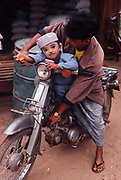 Father and child on a motorbike. Tenasserim district. Burma 2001. Face covered with Thanaka, a yellowish cosmetic paste made from ground bark which is commonly applied to the face in Burma.