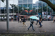 Pedestrians walk past an ad for the latest smartphone displayed on the side of a building in downtown Taipei.