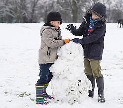 © Licensed to London News Pictures. 14/01/2021. Hexham, UK. Lucas,7, and Emily,6, try to make a snowman enjoy  the snow at Hexham Park following heavy snow last night. Photo credit: Ioannis Alexopoulos/LNP<br /> <br /> ***Permission Granted