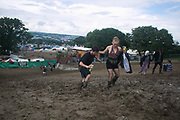A couple of festival goers making their way up a muddy hill, drinks in hand, at Glastonbury Festival 25th July 2016, Somerset, United Kingdom.  The Glastonbury Festival runs over 3 days and has 3000 acts, including music, art and performance and approx. 150.000 attend the anual event.