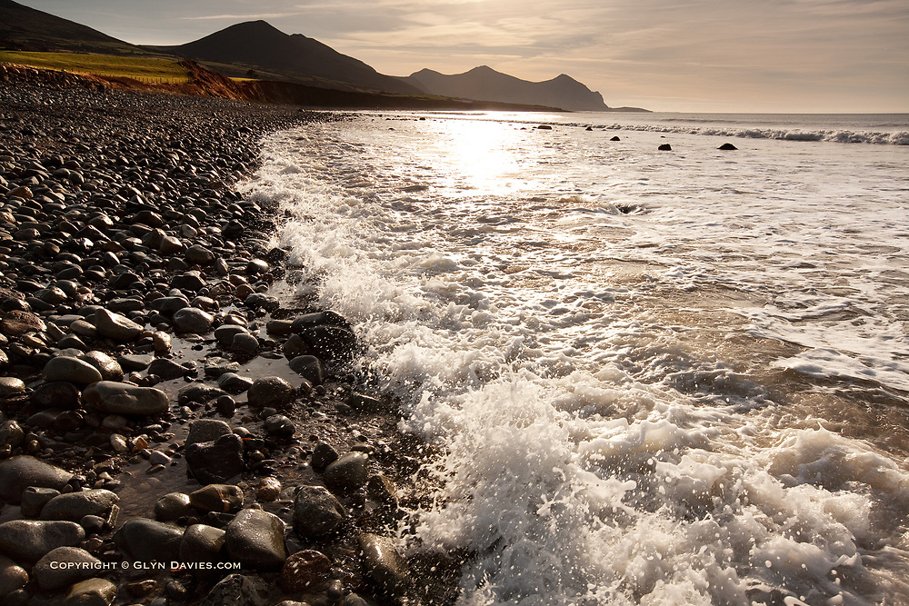 Steep shingle and boulder beach at Aberdesach on the Northern edge of the Llyn Peninsula in North Wales. The mountains of Gyrn Goch, Yr Eifl and Garn For are in the background.