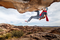 Jacob Garzaon hanging on lip of the Moonshine Roof, Hueco Tanks State Park & Historic Site, El Paso, Texas. USA.