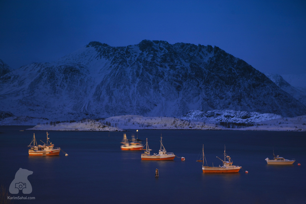 Fishing boats in the bay near the snow-covered Silda Island in the arctic region of Finnmark in Northern Norway.