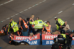 Surrey Police officers try to remove Insulate Britain climate activists from the clockwise carriageway of the M25 between Junctions 9 and 10 where they were protesting as part of a campaign intended to push the UK government to make significant legislative change to start lowering emissions on 21st September 2021 in Ockham, United Kingdom. Both carriageways were briefly blocked before being cleared by Surrey Police. The activists are demanding that the government immediately promises both to fully fund and ensure the insulation of all social housing in Britain by 2025 and to produce within four months a legally binding national plan to fully fund and ensure the full low-energy and low-carbon whole-house retrofit, with no externalised costs, of all homes in Britain by 2030.