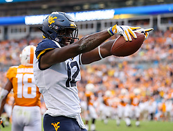 Sep 1, 2018; Charlotte, NC, USA; West Virginia Mountaineers wide receiver Gary Jennings Jr. (12) celebrates after catching a touchdown pass during the third quarter against the Tennessee Volunteers at Bank of America Stadium. Mandatory Credit: Ben Queen-USA TODAY Sports
