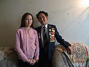 Die jakutische Studentin Natasha mit ihrem Großvater - einem jakutischen Kriegsveteranen der Stolz seine Orden und Auszeichnungen für das Bild zur Schau traegt. Jakutsk wurde 1632 gegruendet und feierte 2007 sein 375 jaehriges Bestehen. Jakutsk ist im Winter eine der kaeltesten Grossstaedte weltweit mit durchschnittlichen Winter Temperaturen von -40.9 Grad Celsius. Die Stadt ist nicht weit entfernt von Oimjakon, dem Kaeltepol der bewohnten Gebiete der Erde.<br /> <br /> Yakutian student Natasha with her grandfather who is a veteran and proudly posing with his medals and decorations. Yakutsk was founded in 1632 and celebrated 2007 the 375th anniversary. Yakutsk is a city in the Russian Far East, located about 4 degrees (450 km) below the Arctic Circle. It is the capital of the Sakha (Yakutia) Republic (formerly the Yakut Autonomous Soviet Socialist Republic), Russia and a major port on the Lena River. Yakutsk is one of the coldest cities on earth, with winter temperatures averaging -40.9 degrees Celsius.