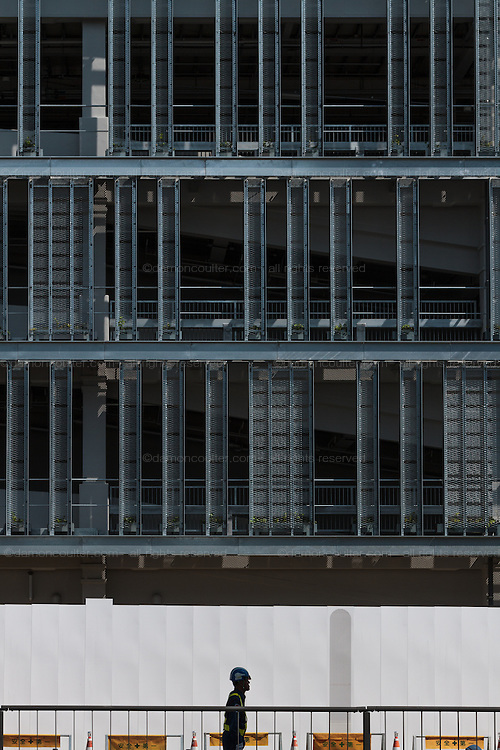 A security guard in silhouette outside the construction site for the new Tsukiji wholesale fish market in Toyosu, Odaiba, Tokyo, Japan Friday June 3rd 2016