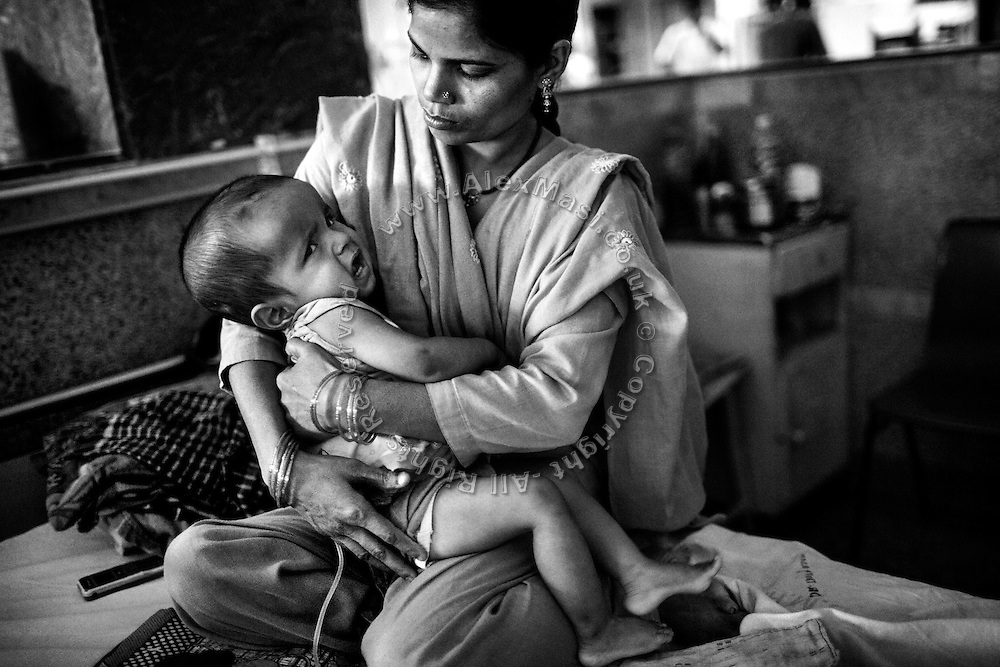 Aliyar, 18 months, a boy suffering severe hydrocephalus, is being held by his mother, Roxana, 31, a '1984 Gas Survivor', while inside the Bhopal Memorial Hospital and Research Centre, in Bhopal, Madhya Pradesh, central India, near the abandoned Union Carbide (now DOW Chemical) industrial complex.