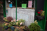 Net curtains and floral display pots past their best, outside a small village cafe, on 25th September 2017, in Rothbury, Northumberland, England.