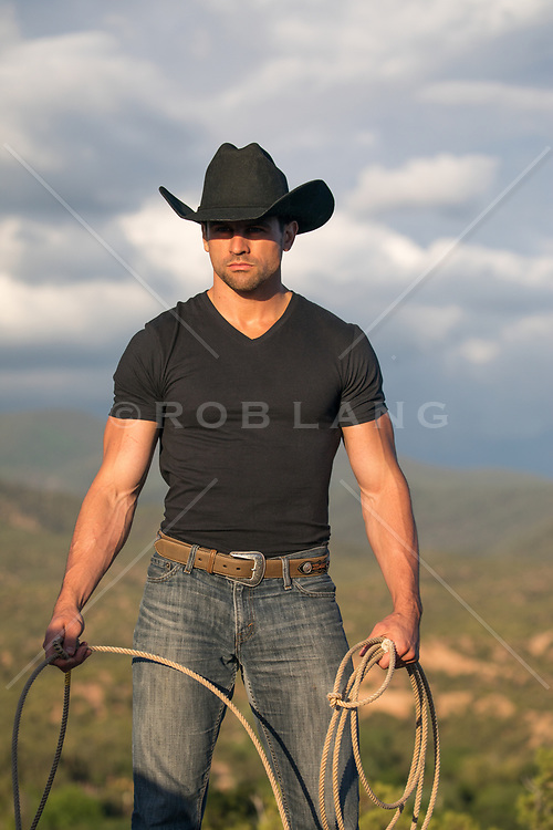 rugged cowboy with a lasso at sunset