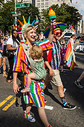 New York, NY - 25 June 2017. New York City Heritage of Pride March filled Fifth Avenue for hours with groups from the LGBT community and it's supporters. A woman dressed as the Statue of Liberty, but in a rainbow-colored robe, and carrying a rainbow torch, carries her child in a carrier.