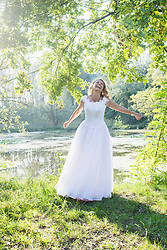 View of a beautiful bride dancing and laughing by lake, Germany