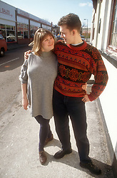 Young man and woman walking down the street arm in arm smiling at each other,
