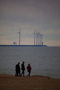 People on the beach at Knokke, Flanders, Belgium, with the wind turbines of Park Wind Farm in Zeebrugge behind.