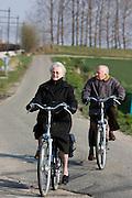 Een ouder stelt fietst door het Zeeuwse landschap